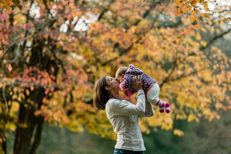 Herbstszene der Mutter junges Baby draußen küssend lizenzfreie stockbilder