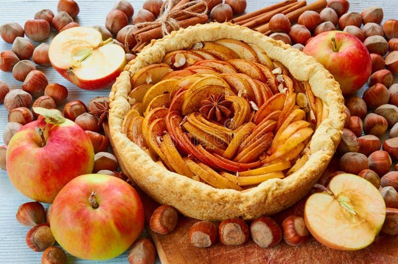 Herbsttörtchen auf dem hölzernen Brett verziert mit frischen Äpfeln, Haselnüssen und Gewürzen - Anissterne und -zimt auf der grau stockfotografie