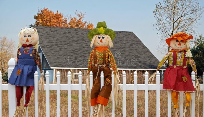 Herbstvogelscheuchenpuppen auf Zaun lizenzfreie stockfotos