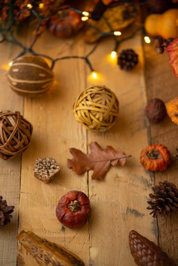 Herbstzusammensetzung mit Blättern und Elementen des Dekors auf einem alten Holztisch mit leuchtenden Lichtern und einer alten La lizenzfreies stockbild