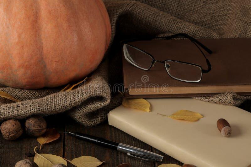 Herbstzusammensetzung mit einem Kürbis und Bücher und Gelb verlässt auf einer braunen Tabelle stockbilder