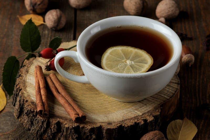 Herbstzusammensetzung mit heißem Tee auf einem hölzernen Stand, Zimt, Hunderose, auf einem braunen Holztisch lizenzfreie stockfotos