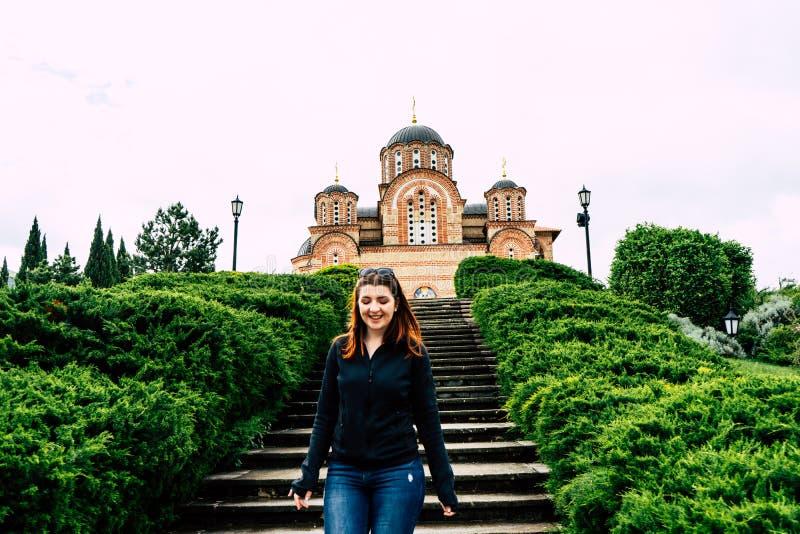 Hercegovacka Gracanica - orthodoxe Kirche in Trebinje, Bosnien und Herzegowina Lächelndes Hinuntergehen des roten Hauptmädchens d stockfotos