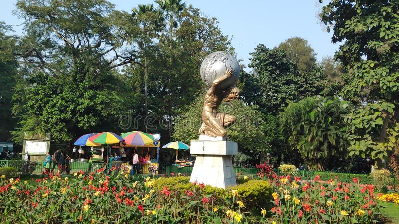 Hercules with globe in center of the garden, covered with little flower trees. royalty free stock photo