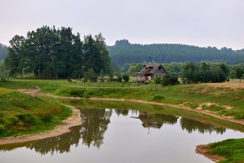 Herdade velha pelo rio em Lituânia Casa de madeira pelo rio fotos de stock