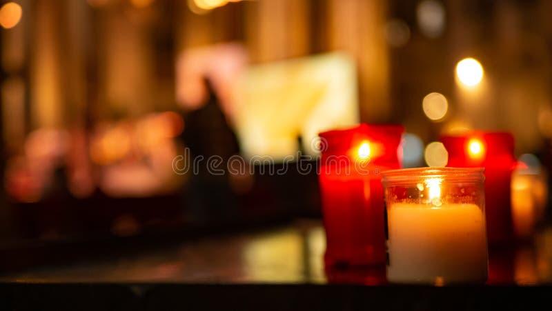 Herdenkingskaarsen in rood en wit glas in kerk stock foto