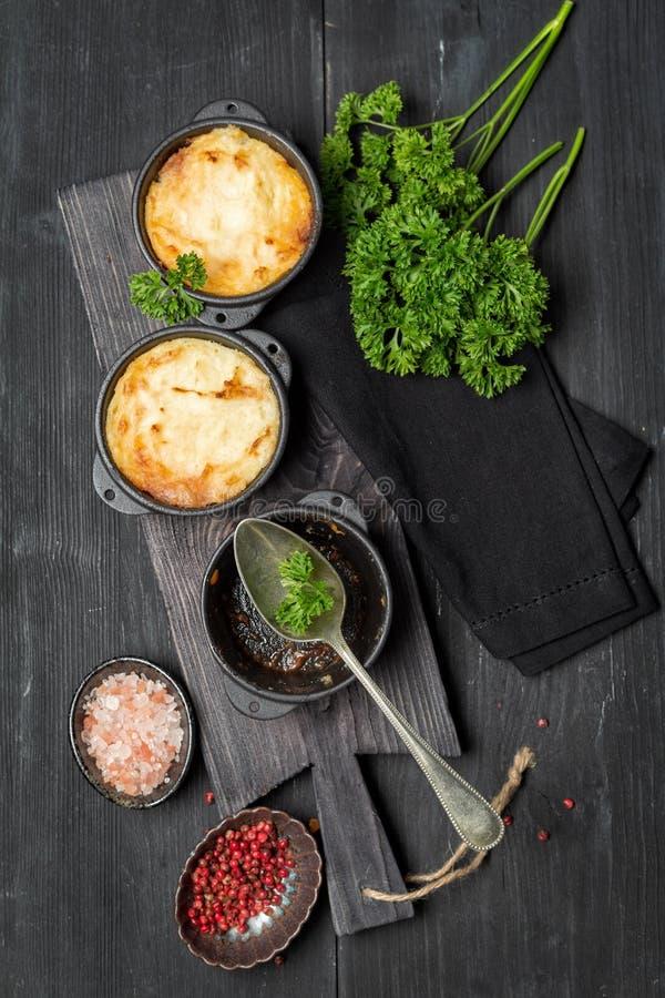 Herdes paj, brittisk eldfast form i gjutjärnpanna, med köttfärs, mosade potatisar och grönsaker, på mörk bakgrund, vertica royaltyfri bild