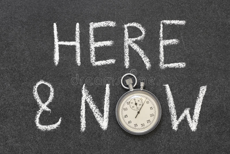 Here and now. Phrase handwritten on chalkboard with vintage precise stopwatch used instead of O royalty free stock photography