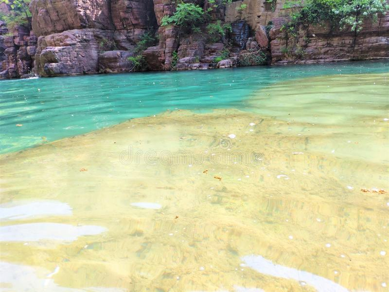 Sparkling crystal clear water pool. Here is a pool of rivers often built in the mountains, which is very happy for the adventurers. The rocks are red, the lake royalty free stock photos