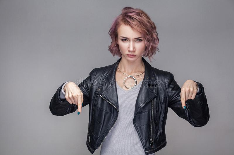 Here and right now. Portrait of bossy serious beautiful girl with short hair, makeup, casual style black leather jacket standing stock image