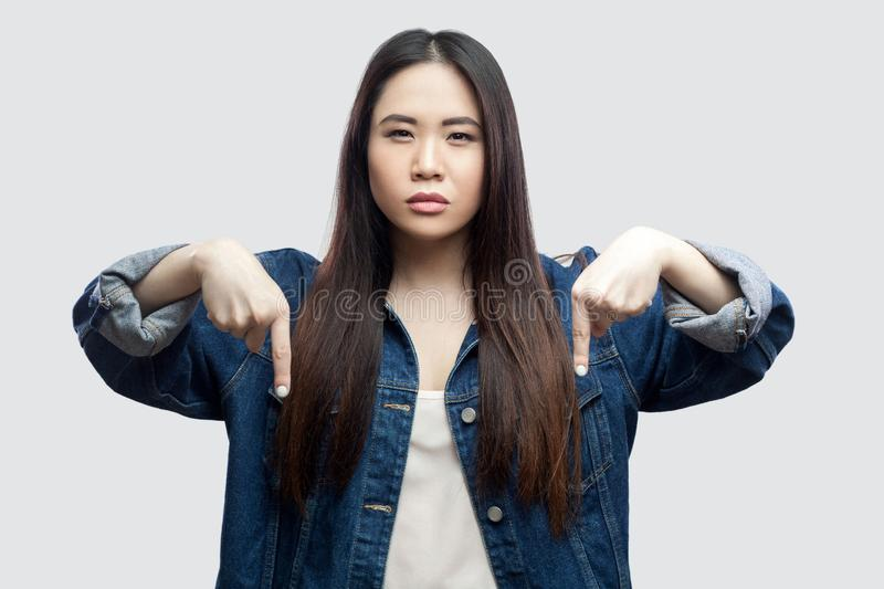 Here and right now. Portrait of serious bossy beautiful brunette asian young woman in casual blue denim jacket with makeup. Standing and pointing down. studio stock image