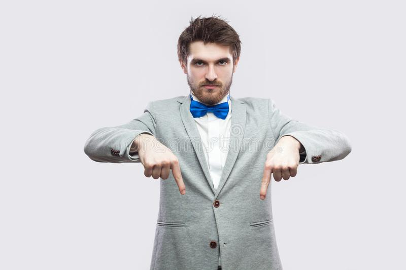 Here and right now. Portrait of serious bossy handsome bearded man in casual grey suit and blue bow tie standing pointing and. Looking at camera. indoor studio stock photos