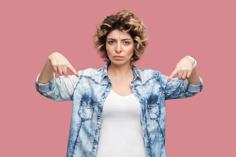Here and right now. Portrait of serious bossy young woman with curly hairstyle in casual blue shirt standing and pointing down and royalty free stock photo
