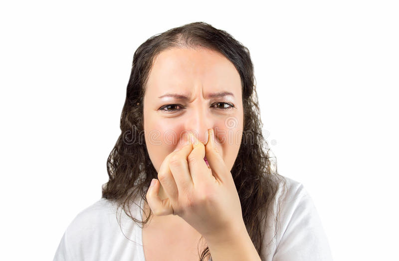 Here's something that stinks. Cropped image of a woman covering her nose and mouth with her hands looking at the camera in concept of disgust and there is a bad royalty free stock image