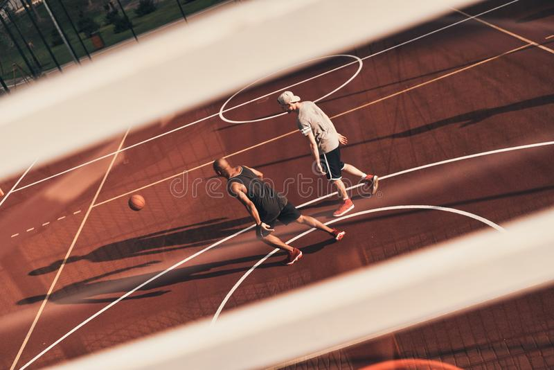 Here to compete. Top view of young men in sports clothing playing basketball while spending time outdoors royalty free stock photos