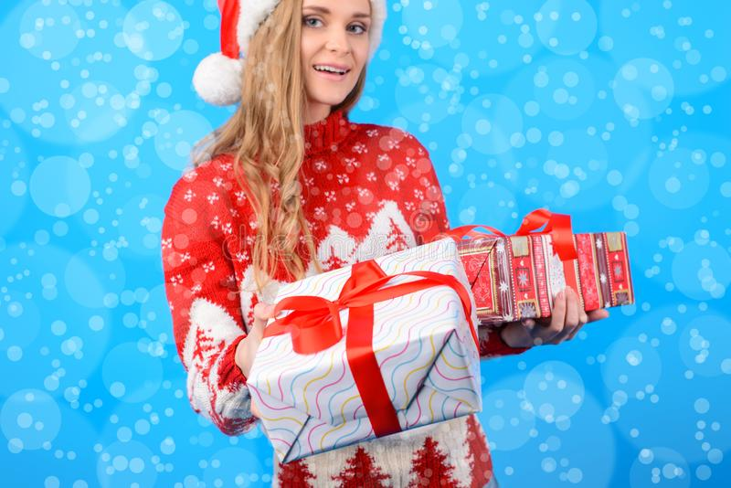 Here you are your present from Santa Claus! Cute lovely attractive smiling woman is giving a present box, isolated on bright blue stock photography