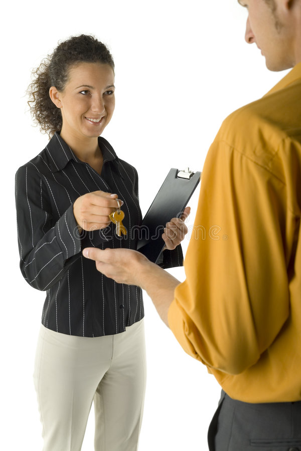 Here is your keys. Young, smiling woman giving keys to the man. Smiling and looking at him. Man is standing back. White background stock photo