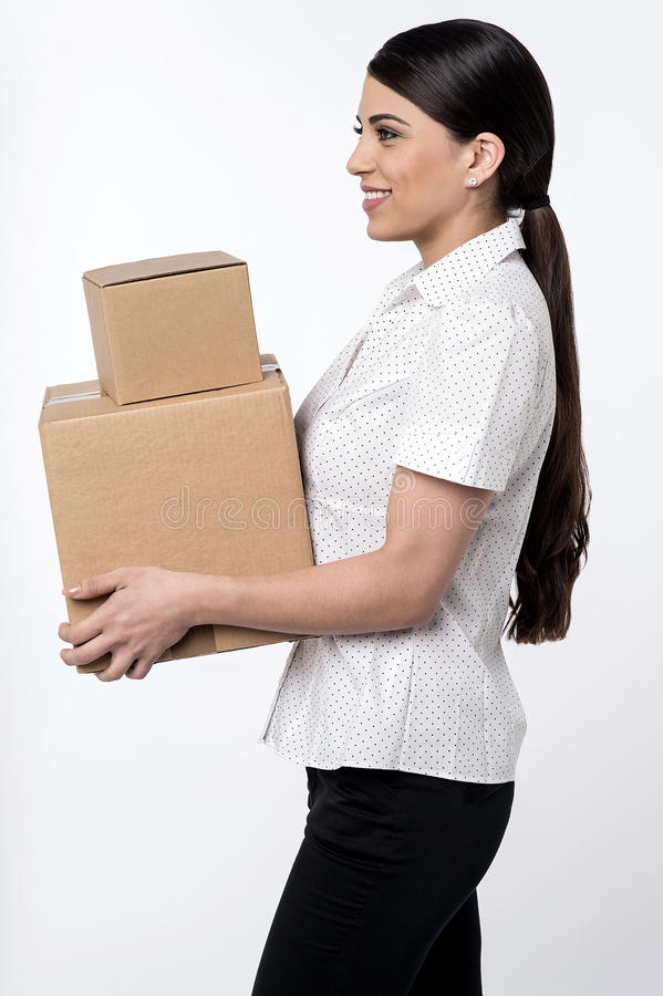 Here is your parcels is sir !. Image of a woman carrying stack of carton boxes stock photography
