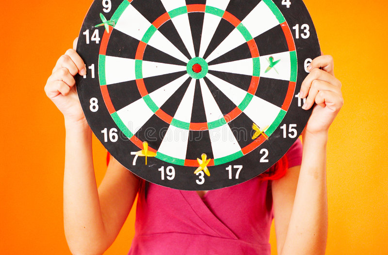 Here is Your Target - 2. Teenager holding up a dartboard as a target to shoot at. Business goals royalty free stock photo