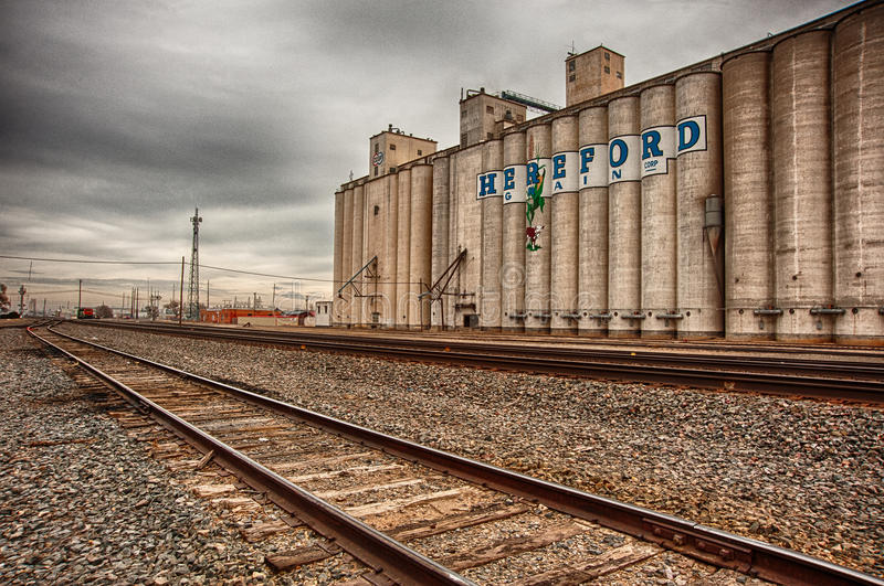 Hereford Grain Corp and Railroad Tracks. Hereford Grain Corp next to the railroad tracks located in Hereford, Texas royalty free stock image