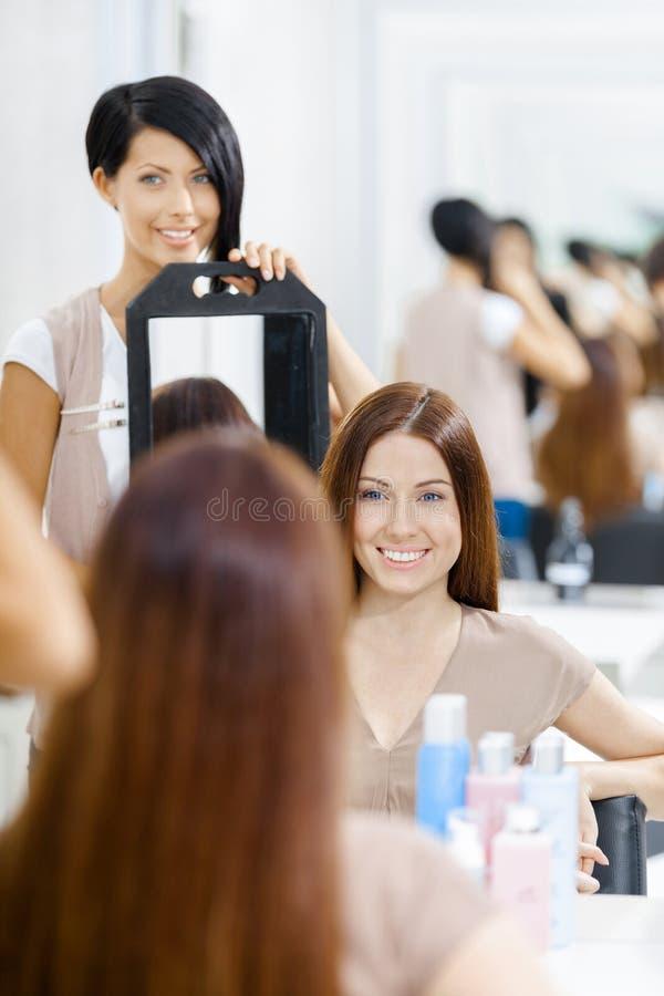 Herenkapper die het kapsel van cliënt in spiegel tonen stock afbeelding