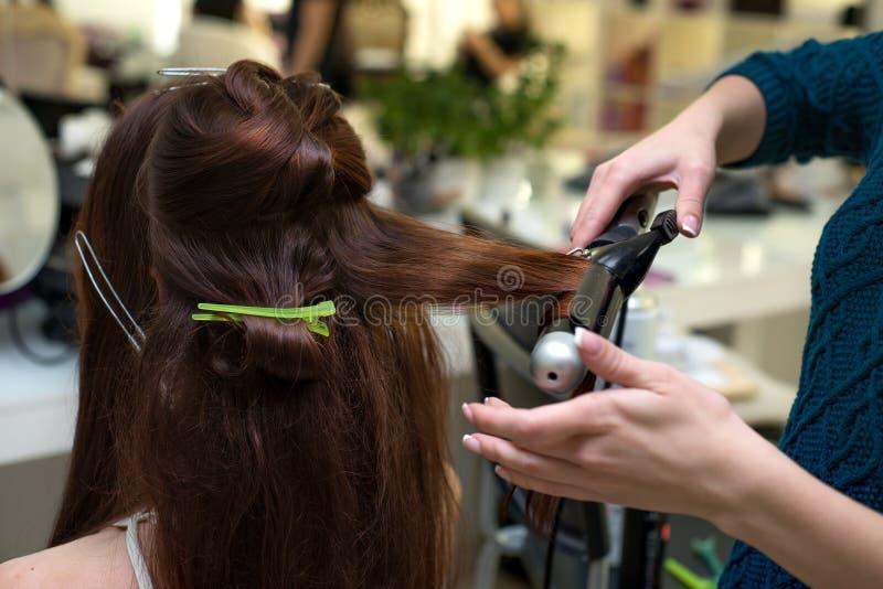 Herenkapper die tot lokken maken aan donkerbruine vrouw Het kapperwerk royalty-vrije stock fotografie