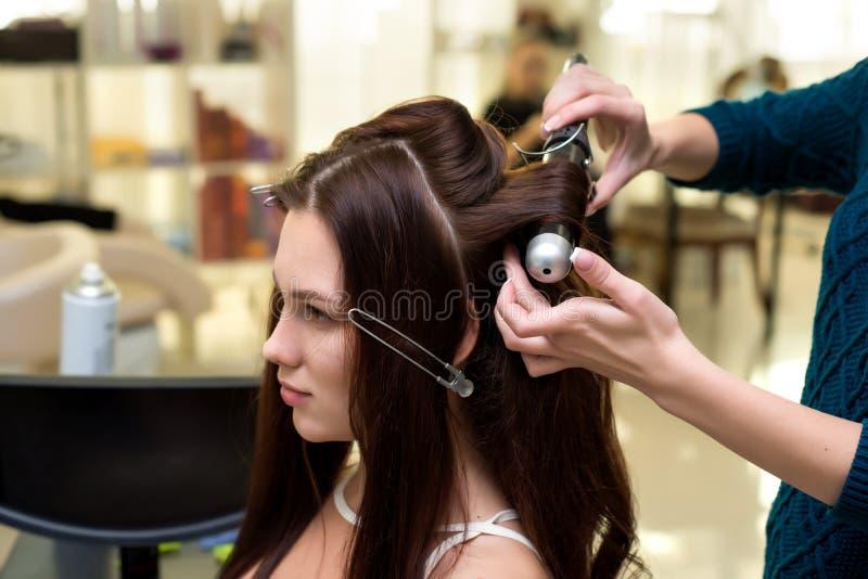 Herenkapper die tot lokken maken aan donkerbruine vrouw Het kapperwerk stock foto's