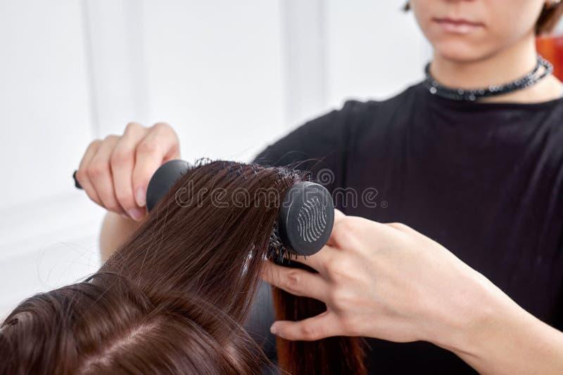 Herenkapper die tot nieuw kapsel maken aan donkerbruine vrouw in salon stock foto