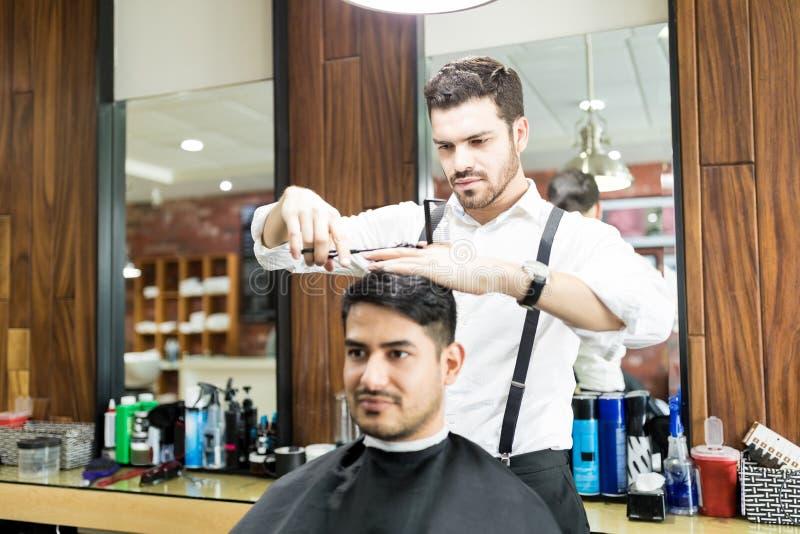 Herenkapper die zich op Scherp Haar van Klant in Salon concentreren royalty-vrije stock afbeeldingen
