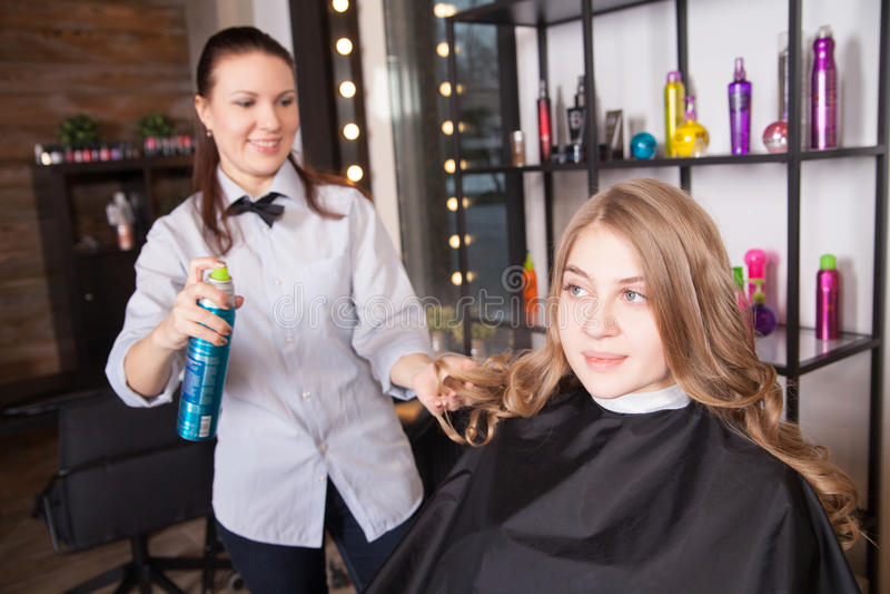 Herenkapper met hairspray en vrouwelijke cliënt royalty-vrije stock afbeeldingen