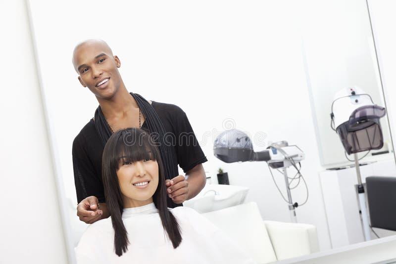 Herenkapper met vrouwelijke klant bij schoonheidssalon stock afbeeldingen