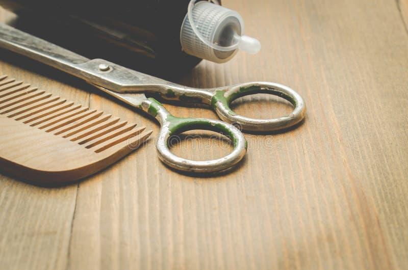 Herenkapperconcept Haarborstels, spuitbus en een schaar op een houten raad, selectieve nadruk en exemplaarruimte stock afbeelding