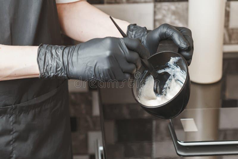 Herenkapperhanden die een kleurstof in een container voorbereiden stock foto