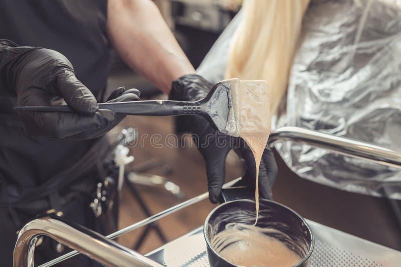 Herenkapperhanden die een kleurstof in een container voorbereiden royalty-vrije stock afbeeldingen