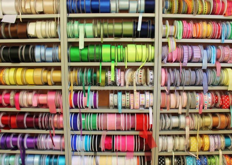 Herenmodezaakplanken van gekleurde lintspoelen en versieringen in stoffenwinkel stock foto