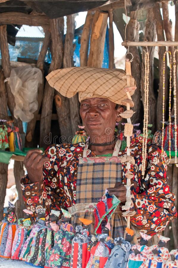 Herero woman in traditional German colonial dress and cow horn hat in front of her souvenir dolls stall, Namibia Africa.  royalty free stock photography
