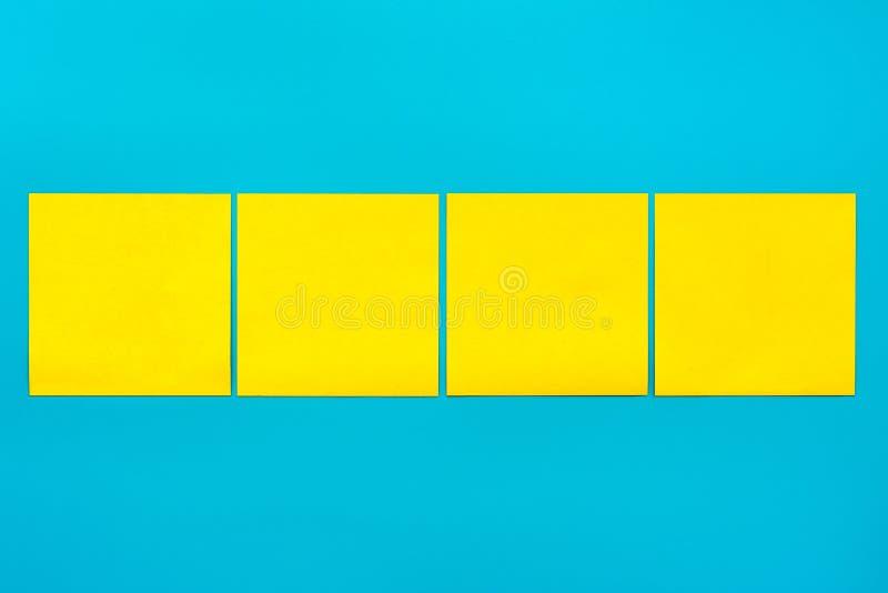 Herinnering en combinatie omhoog bespotten de concepten Dichte omhoog vier gele lege vierkante stickers op blauwe achtergrond met royalty-vrije stock afbeelding