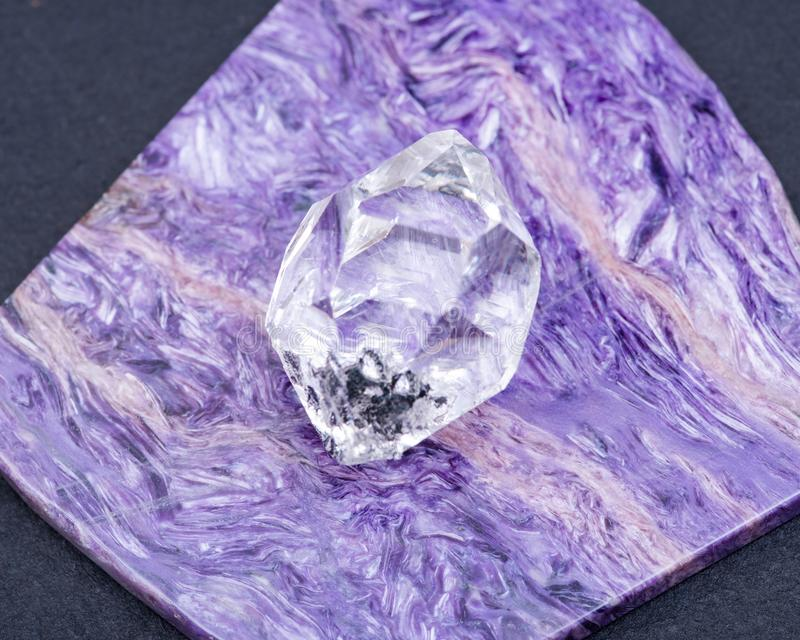 Herkimer Diamond placed on top grade Charoite polished slab from Sakha Republic, Siberia, Russia. On black background. Double-terminated Quartz royalty free stock photos