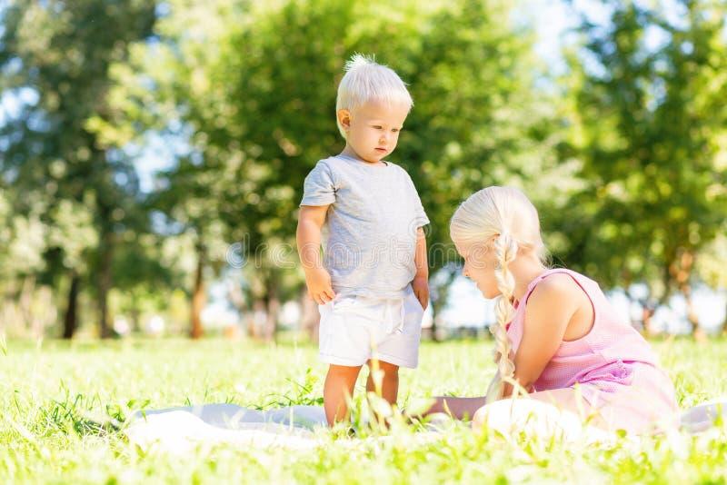 Hermana agradable y hermano que se sientan en la hierba en el parque fotos de archivo libres de regalías