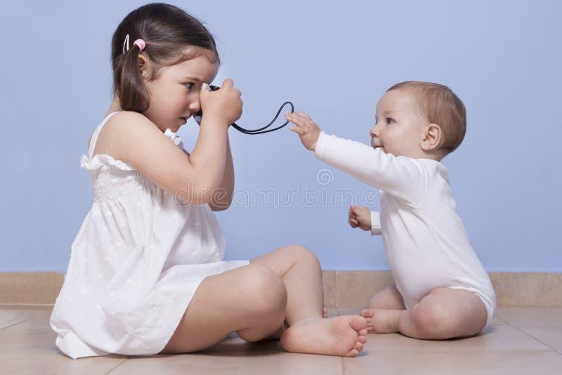 Hermana bastante pequeña que lleva imágenes su hermano del bebé fotografía de archivo libre de regalías