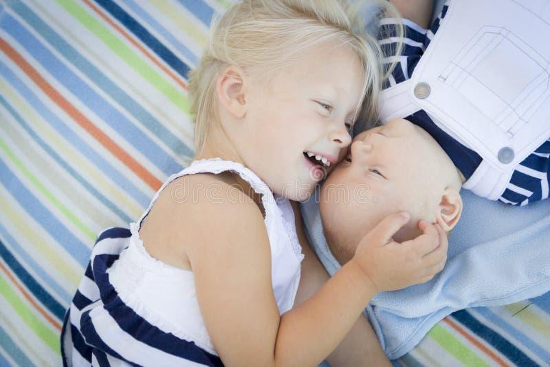 Hermana dulce Laying Next a su bebé Brother en la manta imágenes de archivo libres de regalías
