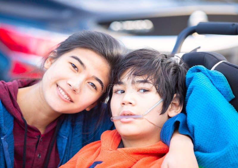 Hermana grande que abraza al hermano discapacitado en silla de ruedas al aire libre, sonriendo foto de archivo libre de regalías