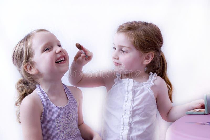 Hermana grande que aplica maquillaje a la pequeña hermana fotografía de archivo