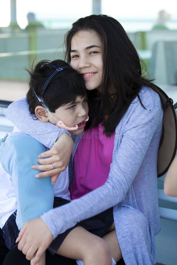 Hermana grande que toma cuidado del pequeño hermano discapacitado foto de archivo libre de regalías