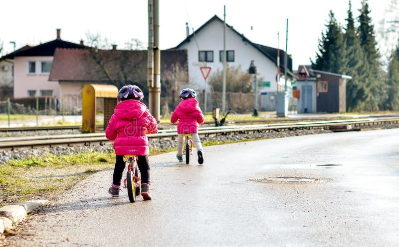 Hermana a los niños que montan las bicis de la balanza en el camino con el casco foto de archivo