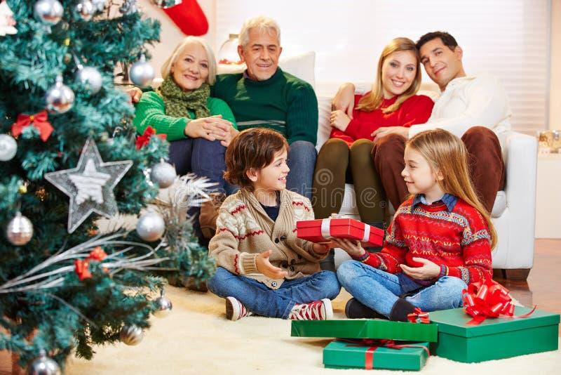 Hermana que da el regalo al hermano en la Navidad fotografía de archivo libre de regalías