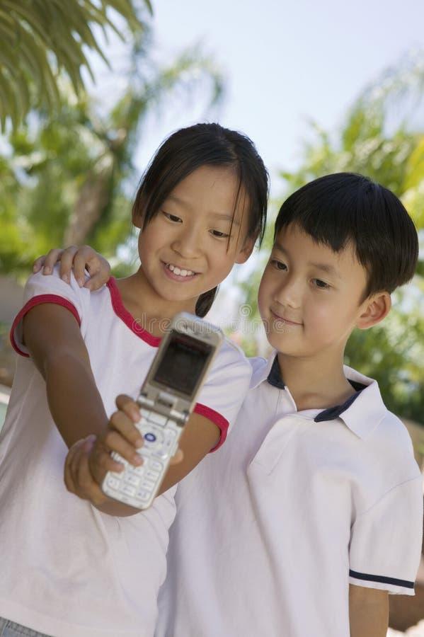 Hermana y Brother que toman la imagen del teléfono de la cámara de ellos mismos en vista delantera del patio trasero fotografía de archivo