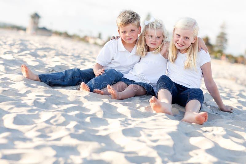 Hermanas adorables y hermano que se divierten en el Bea imagen de archivo libre de regalías