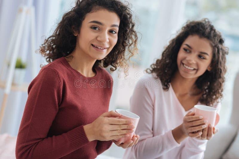 Hermanas alegres que beben té y que pasan el tiempo junto imagen de archivo