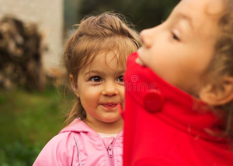 Hermanas alegres que juegan con expresiones grandes en un parque imagen de archivo